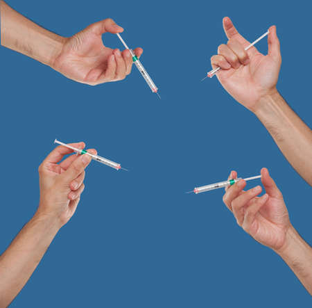 Group of hands holding syringes