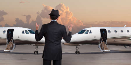 Business man in front of two private jets