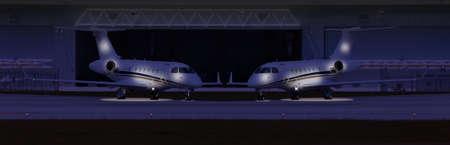 夜の格納庫の前に 2 つの民間航空機