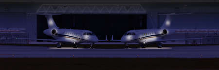Two private planes in front of a hangar at night