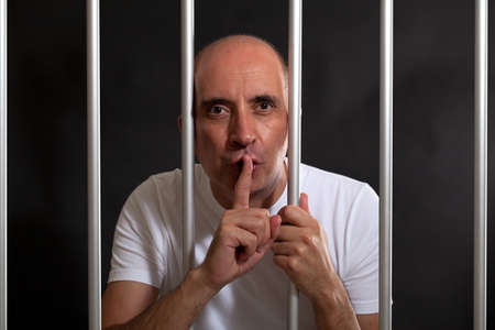 Man in jail gesturing to keep silence Stock Photo