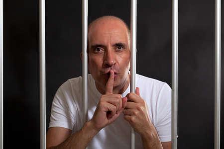 jail: Man in jail gesturing to keep silence Stock Photo