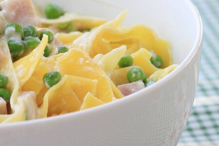 Italian pasta with peas, ricotta and baked ham Stock Photo
