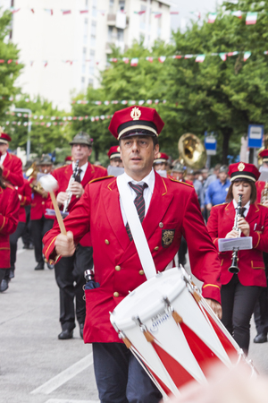 Italian alpine military corps parade happened in Pordenone (Italy), may 2014: a military musical band is walking on the street; portrait of one man playing his instrument