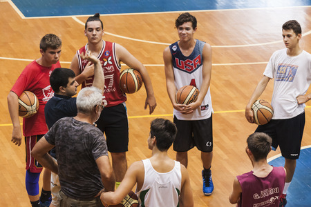 explanations: Basketball team listening to the teacher while he is giving explanations