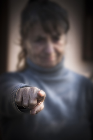 Disapproving woman points finger to you directly Stock Photo