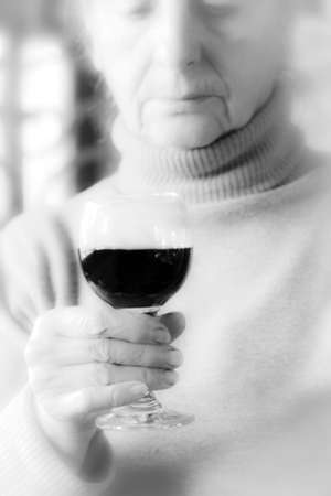 Sad woman holding a glass of red wine - Black and White