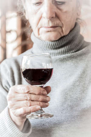 Sad woman holding a glass of red wine Imagens