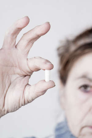 Drug pill kept by a woman with two fingers