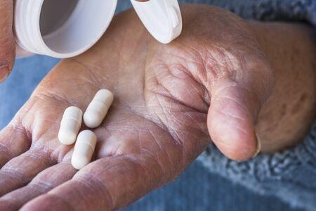 Drug pills on wold omans hand
