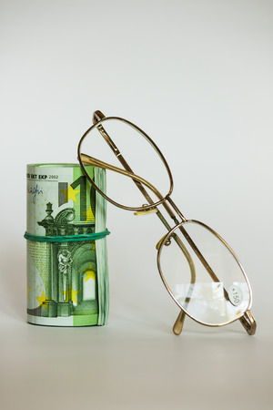 Roller of money and eye glasses Stock Photo