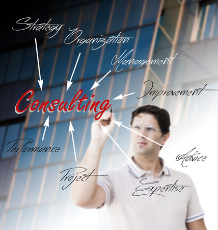 Young man is planning consulting activity by writing many words related to that activity around the word Consulting on a transparent surface in front of himself Stock Photo