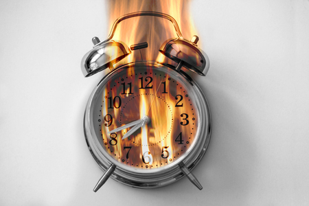 Alarm clock is burning with fire flames