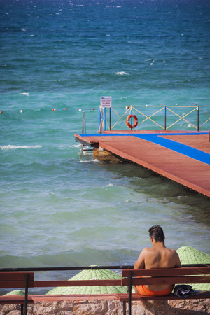 swimsuite: Man sitting on a bench at seaside Stock Photo