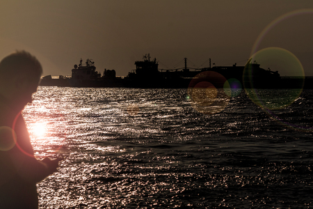 Man using smartphone at the port of ferry boats - backlight
