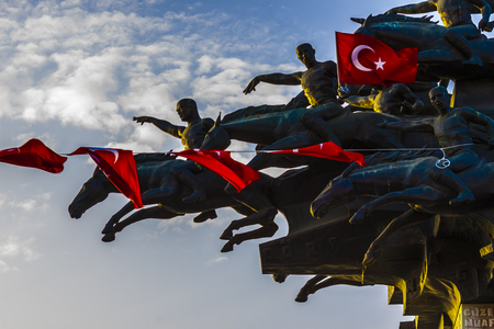 Turkish flags waving in the wind from statue