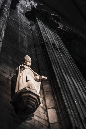 The statue of a priest inside the Cathedral of Milan (Italy).