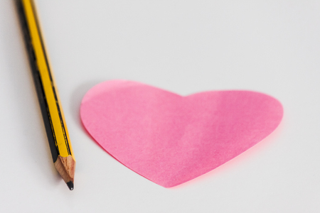 Pink heart note and pencil on white desk
