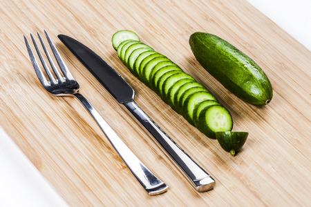 Green cucumbers on chopping board