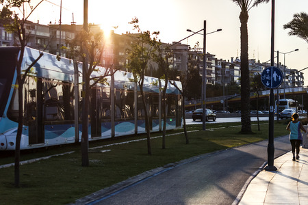 Tram running between the street and the walking path in Izmir Editorial