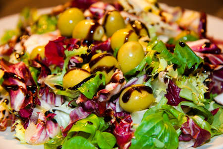 Mixed salad with olives and modena balsamic creamy vinegar photo