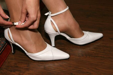 clasp feet: Bride putting on Wedding Shoes