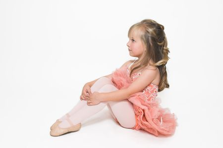 crossed legs: Young ballet dancer wearing an apricot tutu