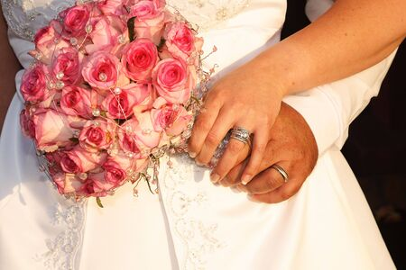 Bridal Couple holding wedding bouquet made of pink roses photo