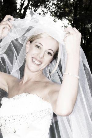 Beautiful Blond bride wearing diamond jewelery on her wedding day photo