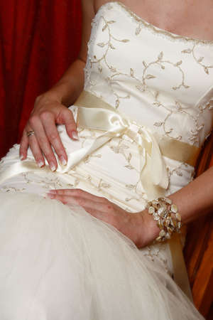 Bride sitting down, close up of detail on wedding gown Stock Photo - 4174513