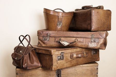 Collection of leather suitcases and bags stacked