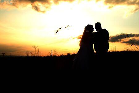 bridal couple: Bridal couple against an orange summer sunset