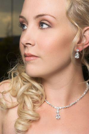 Beautiful Blond bride wearing diamond jewelery photo