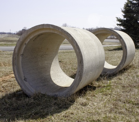Concrete Sewer Pipes waiting in a field   photo