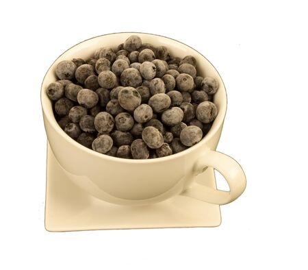 cream colored: Ripe blueberries in a cream colored Large round cup with a square saucer.