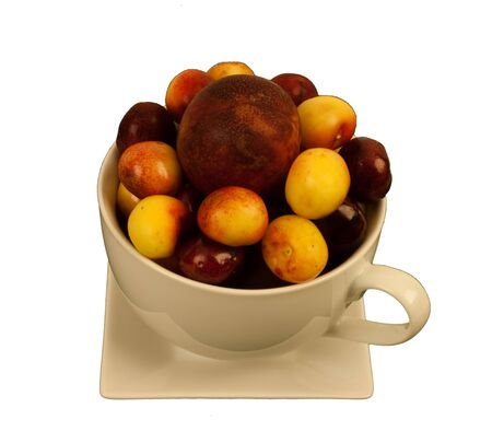cream colored: Two different kinds of cherries & a plum in a large cream colored  cup on a square saucer
