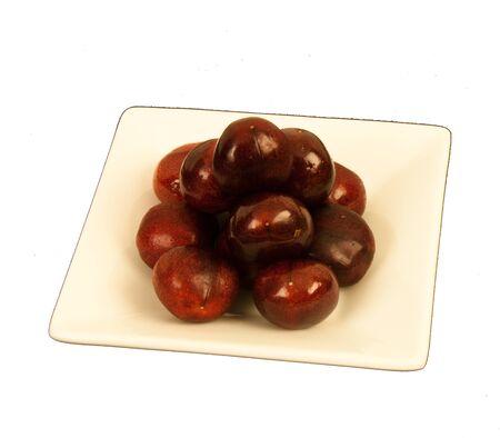 cream colored: Ripe luscious cherries on a cream colored square saucer.