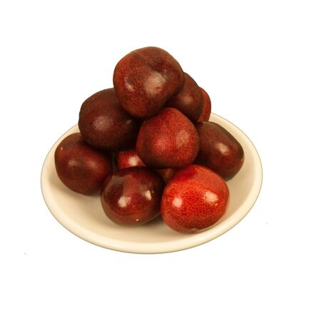 cream colored: Mouth watering burgundy cherries on a cream colored circular dish Stock Photo