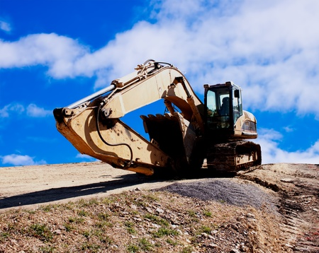 Excavator on construction site with a blue sky photo