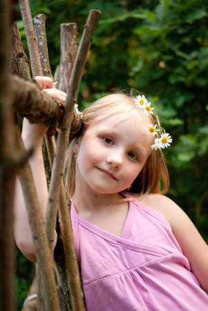 Girl with flowers in hair near wooden palisade photo