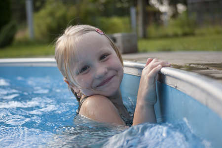 Girl smilimg and swimming  in pool near boundary photo