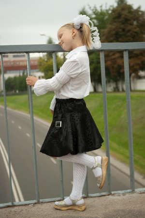 Lonely schoolgirl standing near handhold on bridge photo