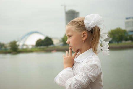 pensive schoolgirl near lake looking far away photo