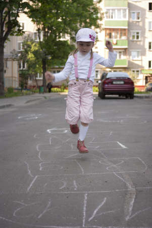 Little girl playing hopscotch at the asphalt photo