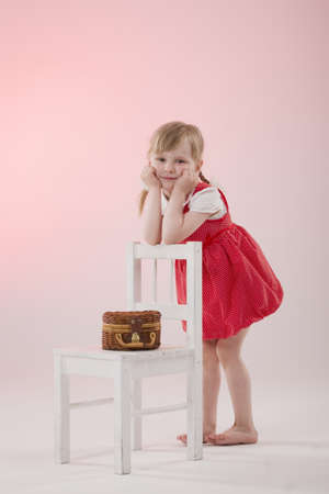 interested baby: Girl in red dress with wicker and pigtails near chair Stock Photo