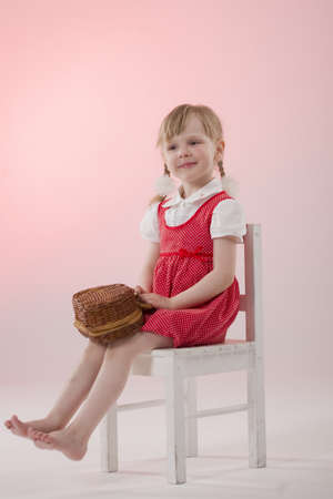 crafty: Girl in red dress with wicker and pigtails on chair