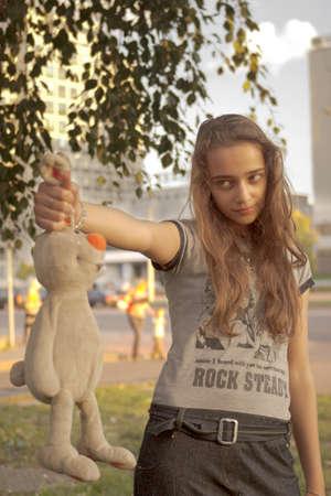 teenage girl holding plush rabbit on ears photo
