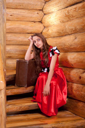 Girl in red spanish dress sitting on stairs in old wooden house photo