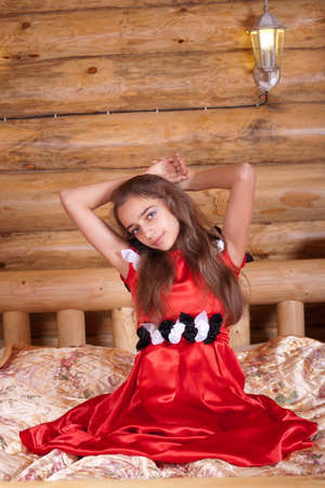Girl in red spanish dress sitting on bed in old wood house photo
