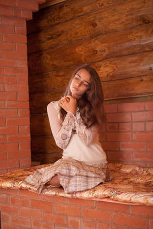 Girl basking on the stove in old wooden house photo